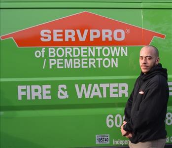 A male employee wearing a SERVPRO uniform in front of a green vehicle.